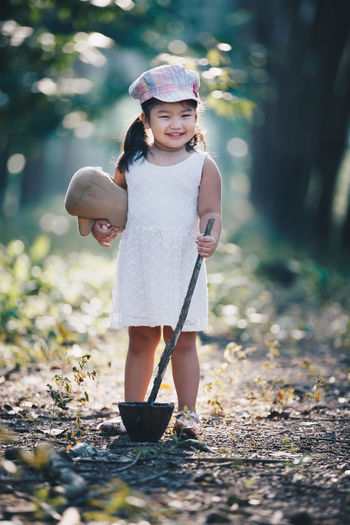 Cap Child Childhood Children Only Cute Day Focus On Foreground Front View Full Length Girls Happiness Holding Innocence Leisure Activity Looking At Camera Nature One Person Outdoors People Portrait Real People Smiling Standing Sun Hat Tree