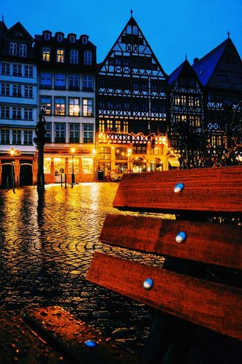 Illuminated buildings by wet street at night
