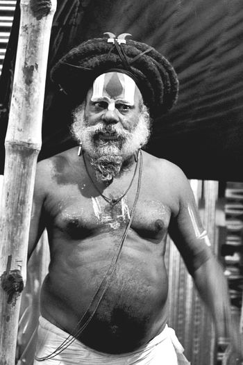 Shirtless bearded sadhu with dreadlocks during kumbh mela