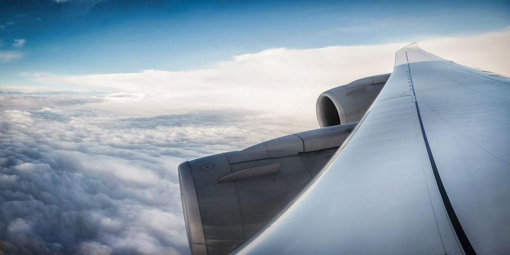 Cropped Image Of Airplane Wing Over Cloudscape