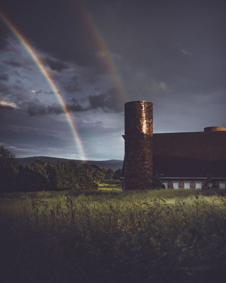 Built structure on field against rainbow in sky