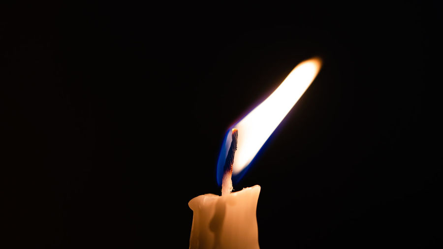 Close-up of hand holding lit candle against black background
