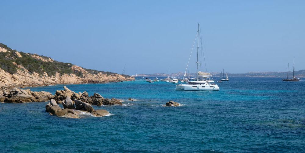 Sailboats on sea against clear blue sky