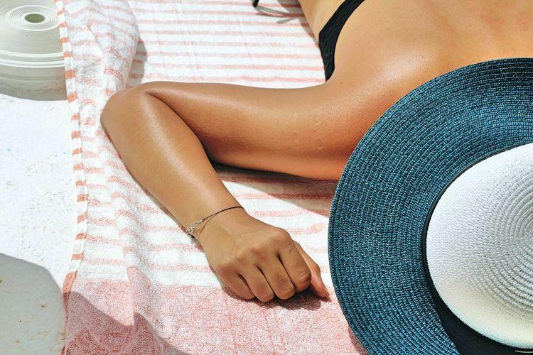 High Angle View Of Woman Sunbathing At Beach