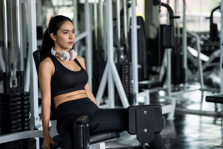 Thoughtful woman exercising in gym