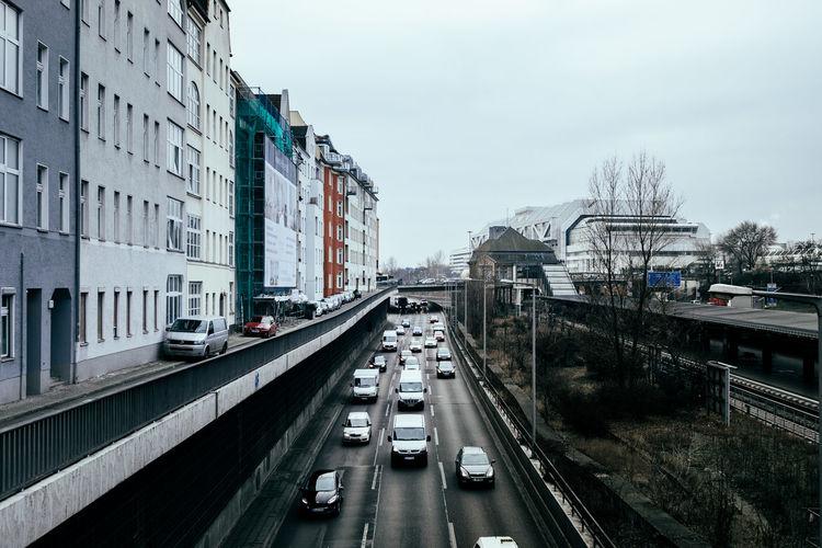 Cars on bridge in city against sky