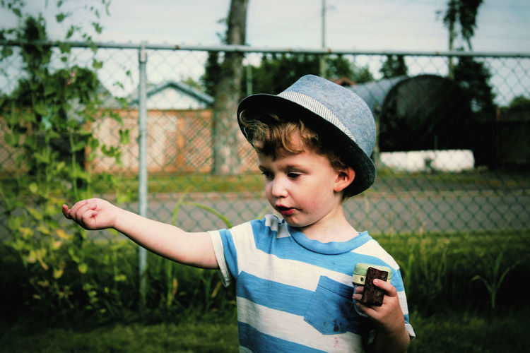 Close-up of boy standing against chainlink fence