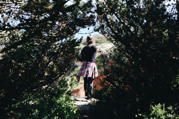 Rear View Of Girl Standing By Tree