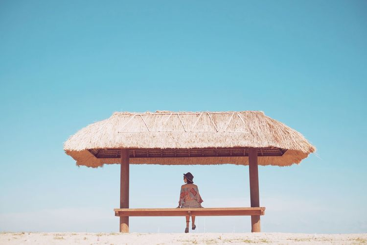 Rear view of woman sitting on seat below thatched roof against blue sky