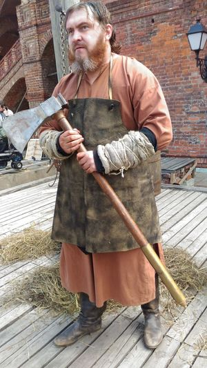 Craftsperson holding axe while standing against brick wall