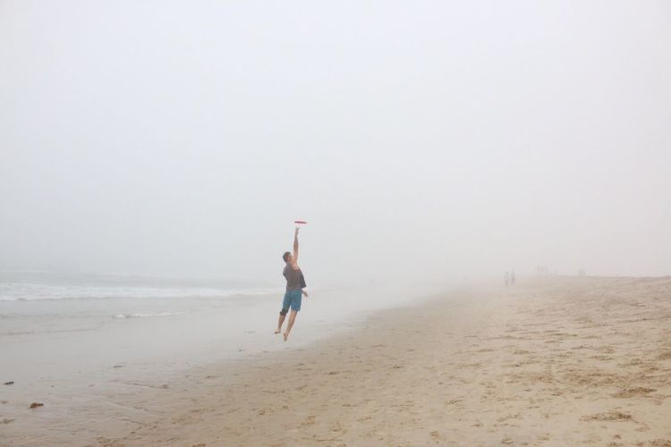 Beachin Tank Top Board Shorts Beach Wear Running Action Shot  Action In The Air Exposure June Gloom May Gray Beach Bum Outdoors Beach Life Cold Temperature Early Morning Excercise Frisbee Land Beach Fog Sand Sky Nature Copy Space