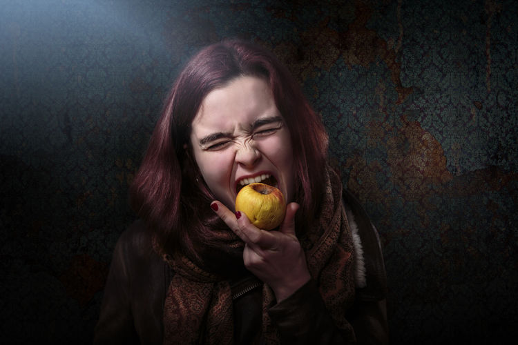 Disappointed woman eating rotten apple against wallpaper