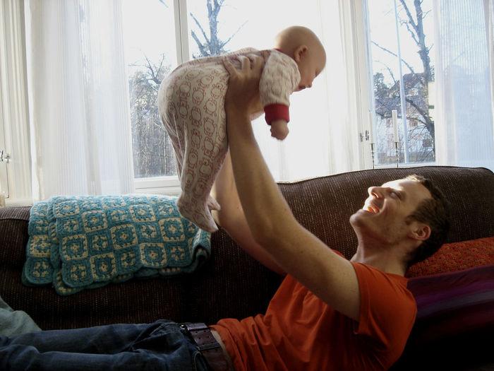 Father Lifting Baby Girl While Lying On Sofa
