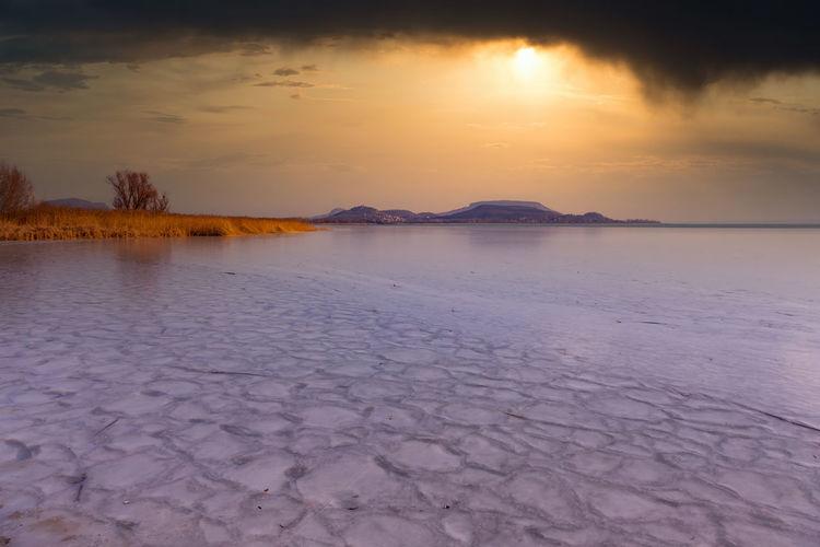 Scenic view of frozen lake against orange sky