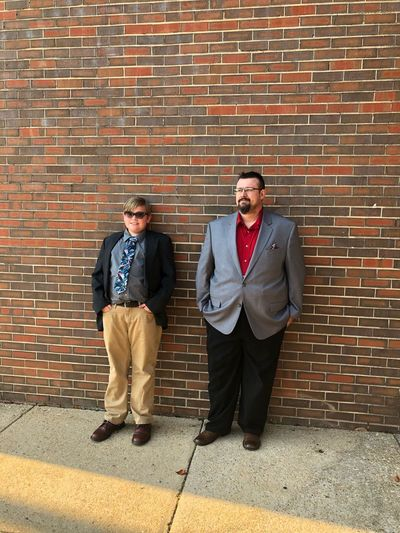 Full Length Of Father And Son In Suits Standing Against Brick Wall