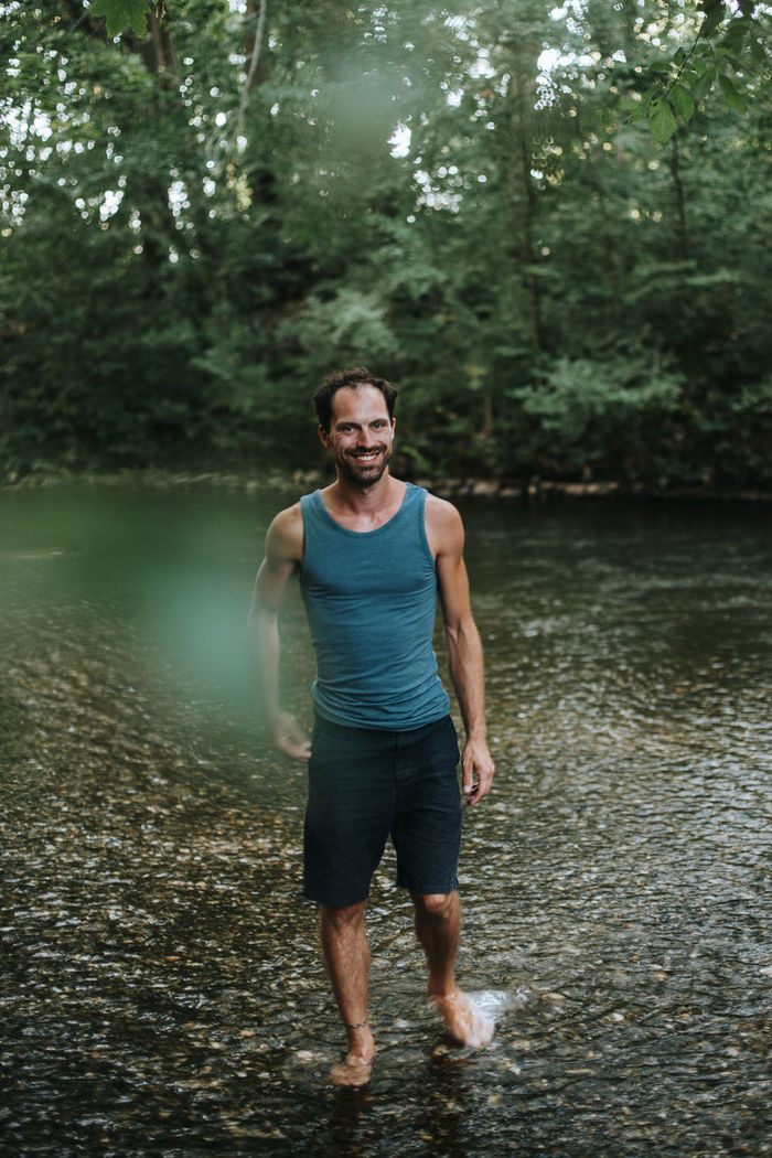 Full length of man standing on river in forest