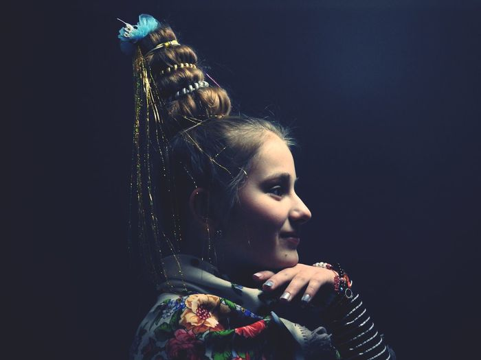 Close-up of girl looking away against black background