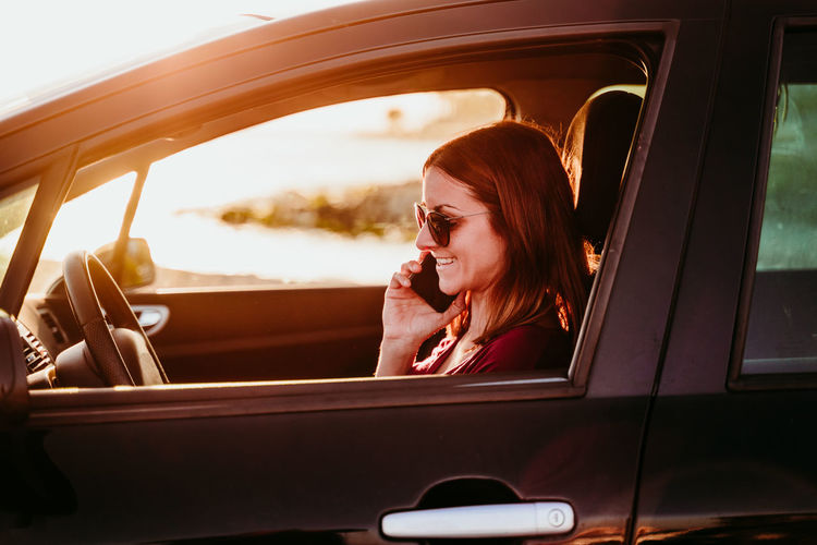 Woman sitting in car and using smartphone