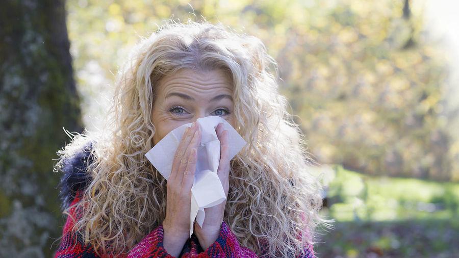Portrait of woman sneezing outdoors