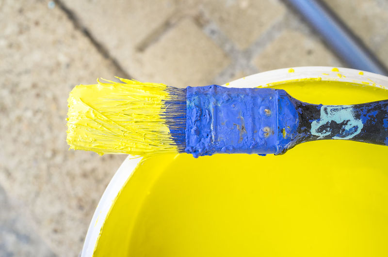 High angle view of blue and yellow container on metal