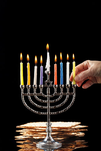 Menorah with lighted candles for Hanukkah on a black in the background. Birthday Birthday Cake Birthday Candles Black Background Burning Cake Candle Chanuka Chanukah Close-up Finger Fire Fire - Natural Phenomenon Flame Hand Hanukkah Heat - Temperature Human Body Part Human Hand Illuminated Indoors  Matchstick Matzo Matzoth Menorah Nature One Person Studio Shot