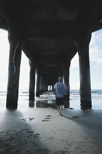Water Beach Below Bridge - Man Made Structure Sea Connection Sand Underneath Architectural Column Architecture Full Length Day Horizon Over Water Nature Outdoors Under Adult People Sky