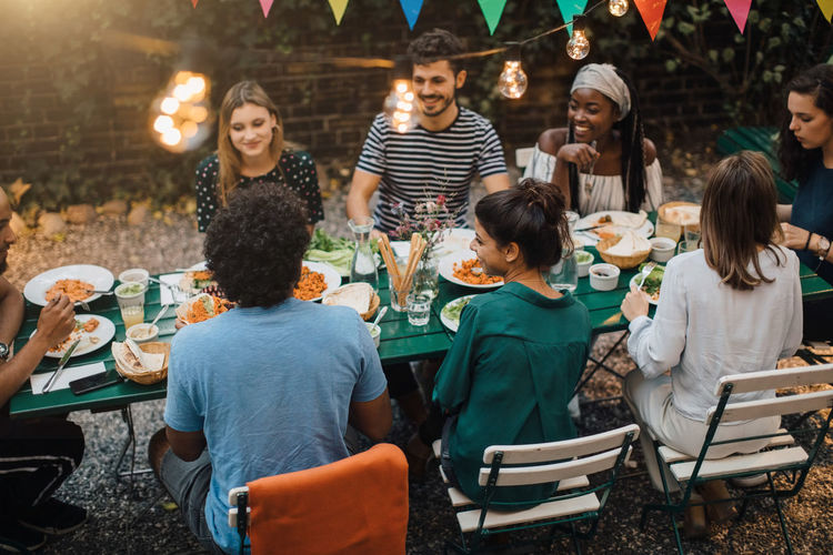High angle view of multi-ethnic young friends enjoying dinner at table during garden party