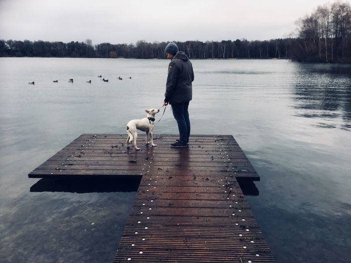 Full length of woman standing with dog on jetty over lake