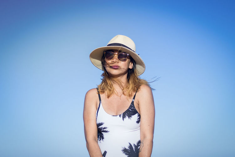 Portrait Of Pregnant Woman In Sunglasses And Hat Against Clear Blue Sky
