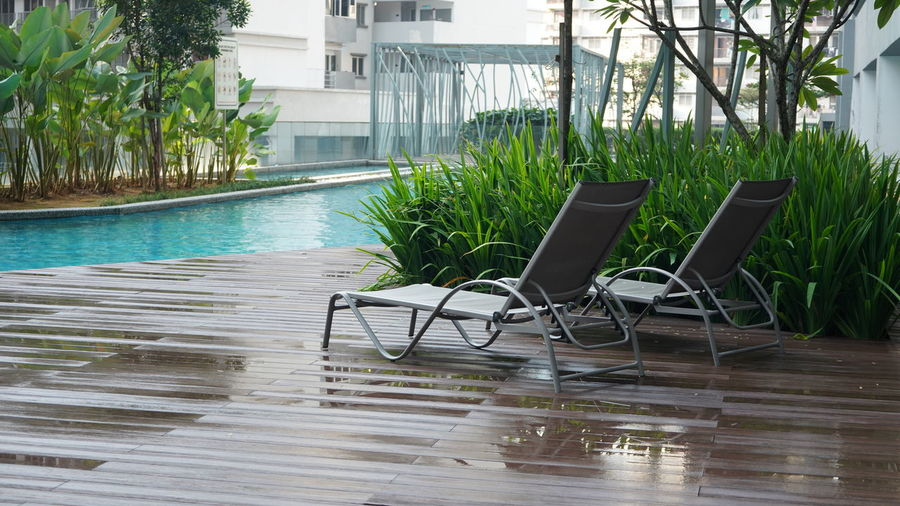 Chairs and table by swimming pool against building