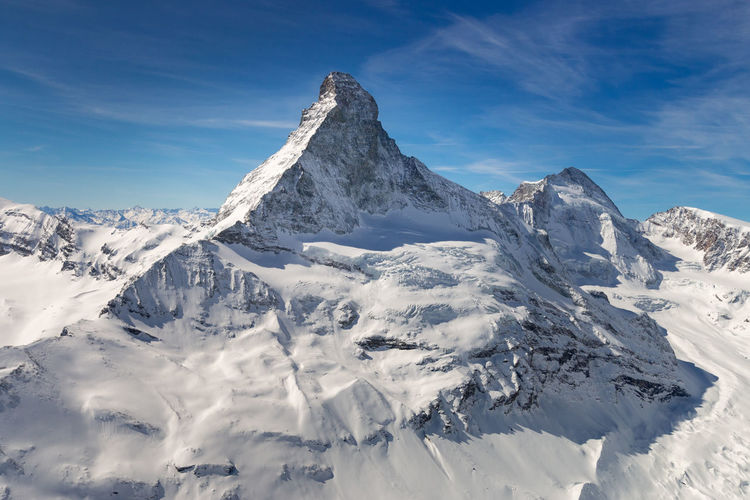 Aerial view of majestic and world famous Matterhorn mountain in front of a blue sky, Switzerland Sky Mountain Scenics - Nature Winter Cold Temperature Beauty In Nature Snow Tranquil Scene Tranquility Snowcapped Mountain Mountain Range Day Cloud - Sky No People Non-urban Scene Nature Blue Environment Mountain Peak Formation Range Majestic Matterhorn  Aerial Landmark