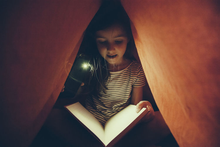 Portrait of girl sitting on book