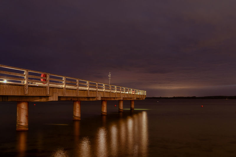 Small illuminated pier at night in the baltic sea with reflective light trails on the water