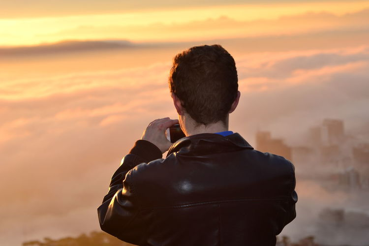 Soaking it in Architecture Beauty In Nature Built Structure Cloud - Sky Day Headshot Jacket Leisure Activity Lifestyles Men Nature One Person Orange Color Outdoors People Photographer Real People Rear View Sky Standing Sunrise Sunset