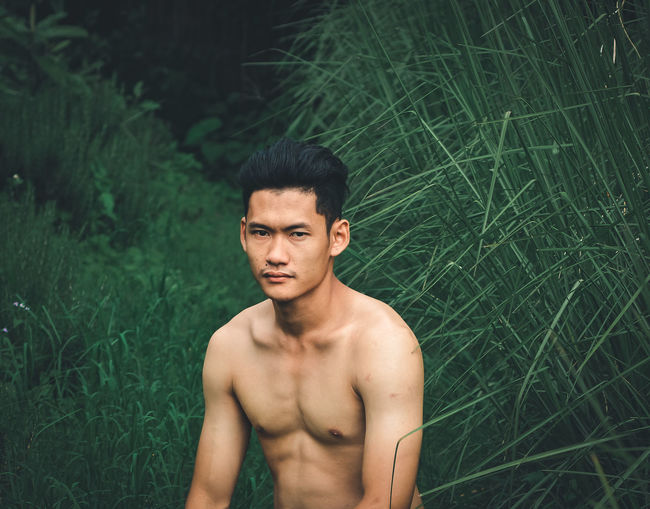 Portrait of shirtless young man standing on land