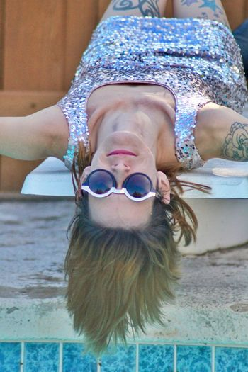 Portrait of young woman wearing sunglasses and shiny dress while lying on poolside