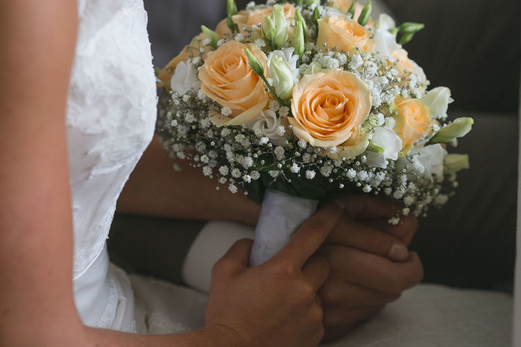 Midsection Of Bride And Groom Holding Rose Bouquet