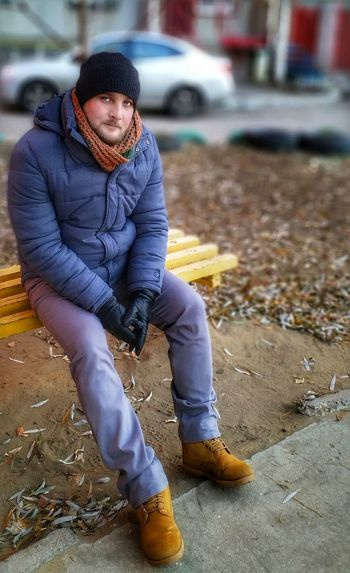 Portrait of man wearing hat sitting outdoors during winter