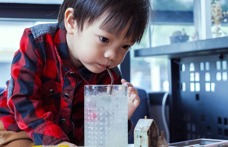 Cute boy drinking juice on table in restaurant