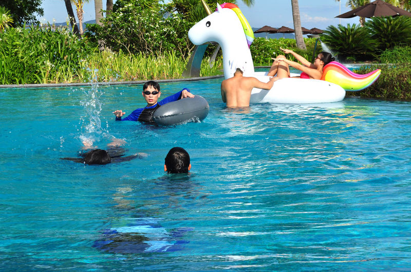 Guests playing in swimming pool at Angsana resort, Laguna Lang Co, Vietnam. Boys Couples Editorial  Fathers Flotation Fun Leisure Leisure Activity Lifestyle Lifestyles Lăng Cô Outdoors Playing Recreation  Resorts Sons Summer Swimming Swimming Pools Togetherness Tourism Tree Unicorn Vacations Water