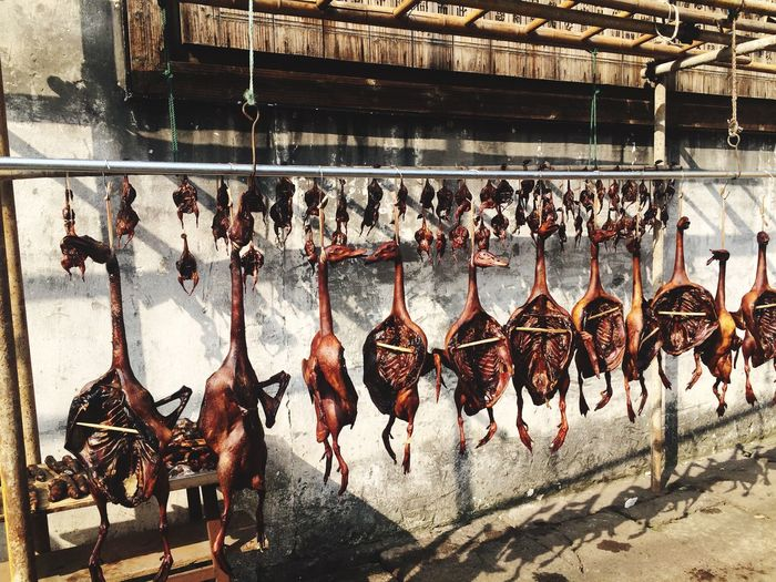 Roasted Ducks Hanging By Wall At Market Stall