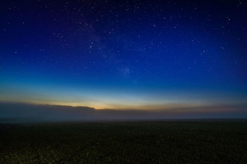Scenic view of foggy night field against starry dark blur sky