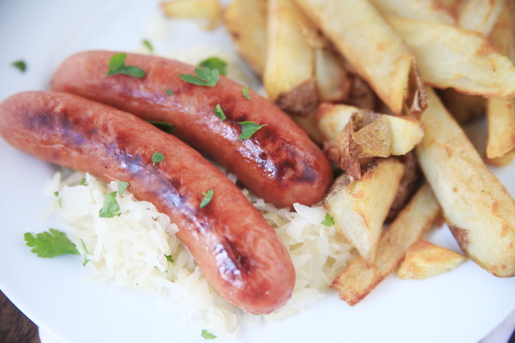 Sausages on sauerkraut with fries Cilantro Close-up Fried Potatoes Hearty Food Home Cooking Home Fries Indoors  Lunch Main Course Meal Meat And Potatoes Natural Light No People Plate Platter Ready-to-eat Sauerkraut Sausages Savory Food Textures Vegetables