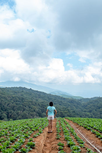 Full length of woman standing on agricultural field against sky