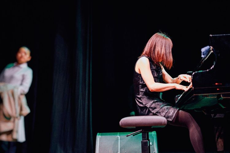 Woman playing piano on stage