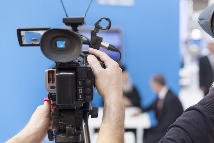 Cropped Hands Of Male Tv Reporter Holding Television Camera