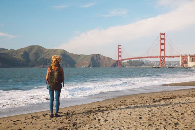 Rear view of woman standing on shore against golden gate bridge