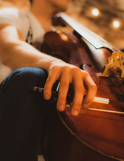 Midsection of man holding cello