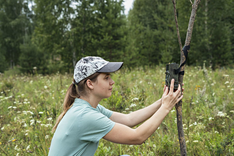 Young woman zoologist sets camera trap for observing wild animals in forest ,collect scientific data