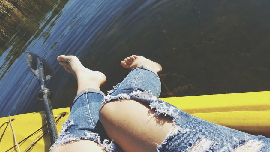 Low section of woman wearing torn jeans sitting on boat in lake